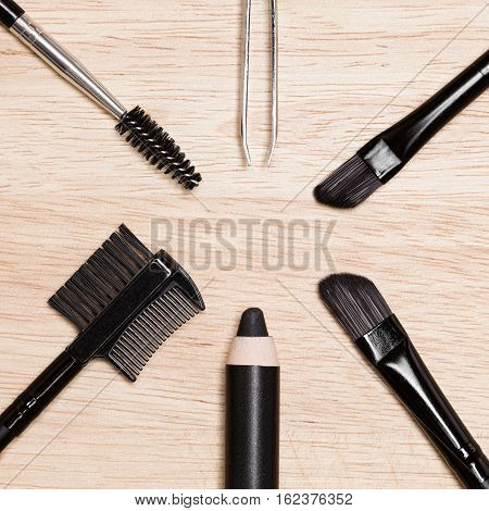 Accessories for brows care: brow comb / brush, spooly brush, angled brushes, eyebrow pencil, tweezers on wooden surface. Eyebrow grooming tools
