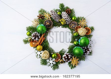 Christmas wreath dried oranges pine cones and cinnamon sticks. Christmas greeting background with green balls and rustic ornaments.
