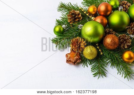 Green Christmas ornaments fir branches golden pine cones and baubles. Christmas greeting background with holidays decoration. Copy space.
