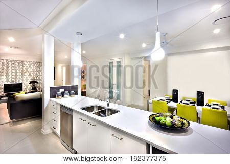 Indoor hanging lights over the counter next to dining table set up with chairs there are fruits on a dish near to silver sink and tap. There are entrances to rooms