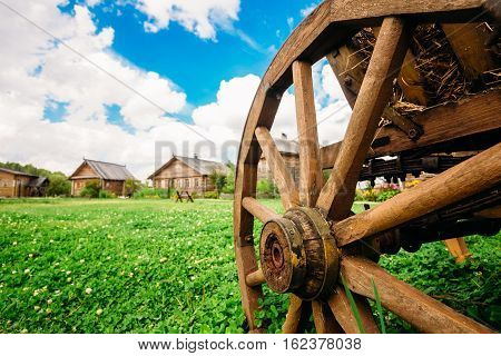 Wooden cart wheel in the foreground. In the background wooden hut Slavic rural type