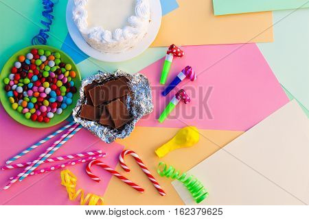 Cake, candy, chocolate, whistles, streamers, balloons on holiday table. Concept of children's birthday party. View top.