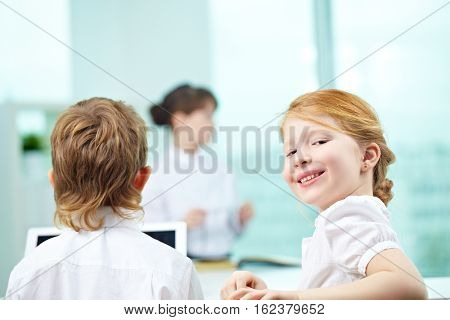 Smiling little girl in formalwear sitting in office and looking at camera