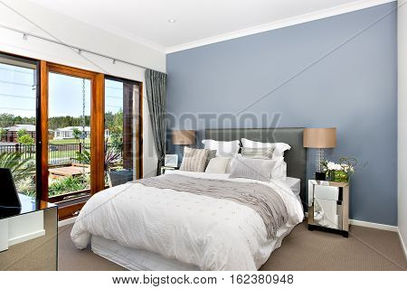Modern decorative bedroom included king size bed with white sheets over it. There is a gray color wrap or rob lay on the bed. Small silver cupboards with table lamp top of it from both sides of the bed. The outside can be seen from the wooden window white