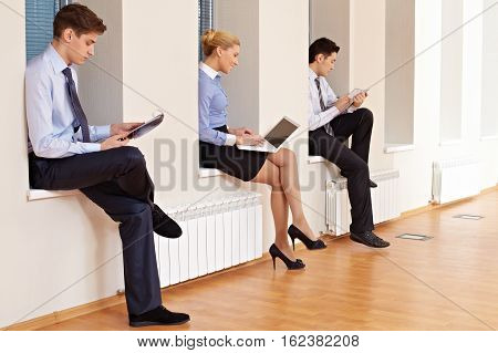 Three business colleagues sitting on window-sill and working