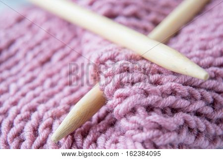 Two knitting bamboo spokes and pink knitted wool fabric close up, selective focus
