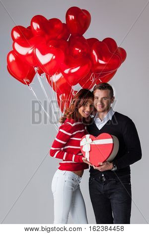 Couple with heart shaped balloons and gifts, Valentines day
