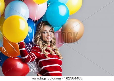 Happy woman with many colorful balloons