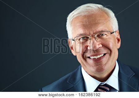 Portrait of senior businessman in eyeglasses looking at camera and smiling