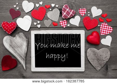 Chalkboard With English Text You Make Me Happy. Many Red Textile Hearts. Grey Wooden Background With Vintage, Rustic Or Retro Style. Black And White Style With Colored Hot Spots
