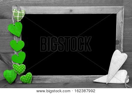 Chalkboard With Copy Space For Advertisement. Green Hearts. Wooden Background With Vintage, Rustic Or Retro Style. Black And White Image With Colored Hot Spots.