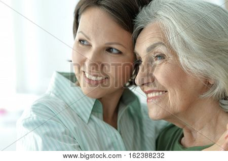senior mother with adult daughter, posing together
