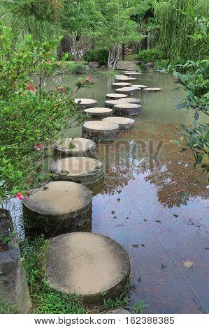 Element of landscape design a stone path across the pond