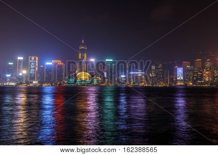 Hong Kong, China - January 1, 2016: Hong Kong skyline seen from the waterfront of Tsim Sha Tsui in Kowloon. On background the landmarks of Central Plaza and Hong Kong Convention and Exhibition Centre.