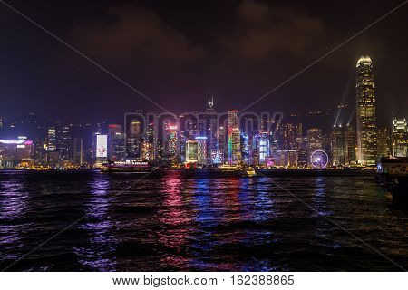Hong Kong, China - January 1, 2016: Hong Kong skyline seen from the waterfront of Tsim Sha Tsui in Kowloon with the landmarks of Bank of China Tower, HSBC Building, Two International Finance Centre.