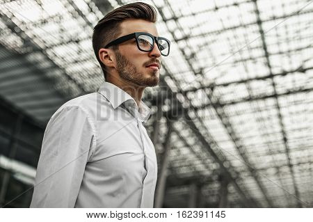 Close-up of handsome businessman in white shirt and glasses checking time on street while waiting for someone on the office building background.