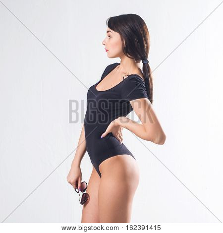 Studio portrait of a young woman with perfect body, wearing one piece bodysuit