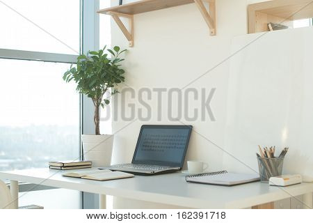 Side view picture of studio workplace with blank notebook, laptop. Designer comfortable work table, home office