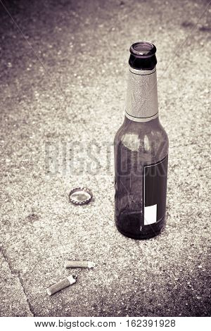 Bottle of beer resting on the ground with three cigarette's butts. Toned image