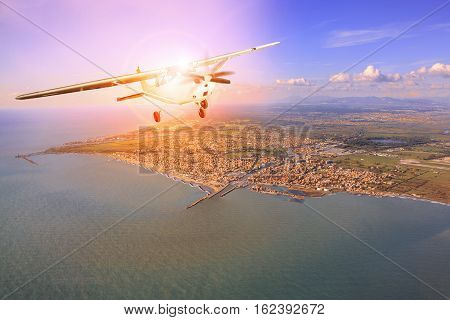 propeller plane flying over coastal of towkn sun light behind