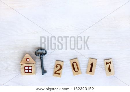 Concept finished house with a key and digits on wooden plates denoting year / individual housing in 2017
