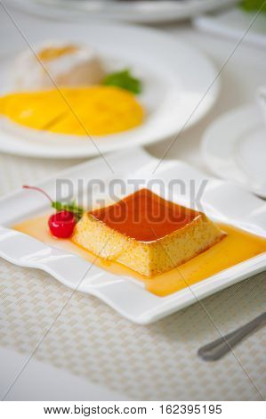 caramel pudding and melted sugar decoration on white plate