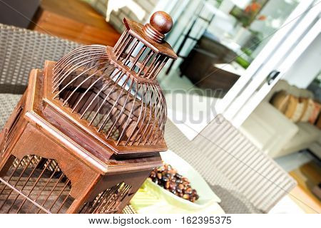Wooden ornamental item made in wooden like a bird cage in a luxury room. This may be a traditional wooden item use in Asian religion