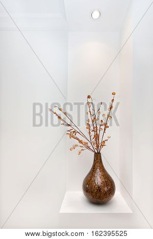 Shiny vase is probably made by pasting small wooden parts together shaping as a bottle gourd there some sticks with buttons fixed to the vase and kept on the wall cupboard
