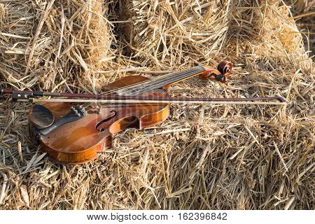 One violin and bow placed on a pile of straw in the field under the evening sun.