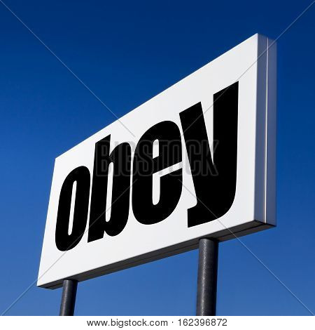 Horizontal billboard with the order to OBEY against irreal blue sky. Abstract concept of consumerism human mind control power of corporations and lobbies.