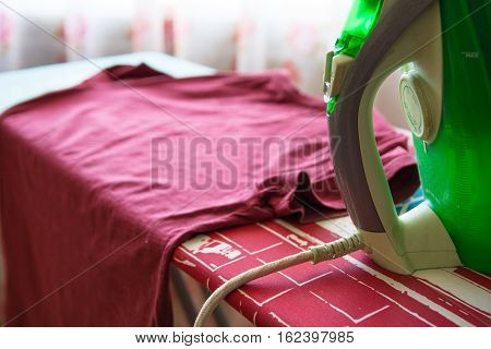 Shirt and iron on ironing board. Homelike atmosphere.