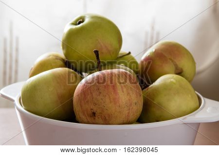 Green and red wet apples in a white bowl