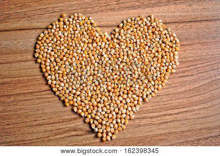 Popcorn kernels in a heart shape on a wooden table