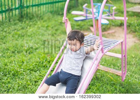 Little Asian Kid Playing Slide At The Playground Under The Sunlight In Summer