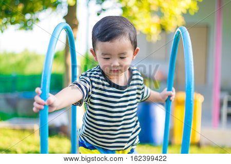 Little Asian kid playing slide at the playground under the sunlight in summer Kids play on school yard. Happy kid in kindergarten or preschool. shallow DOF