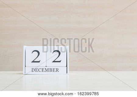 Closeup surface white wooden calendar with black 22 december word on blurred brown wood desk and wood wall textured background with copy space selective focus at the calendar