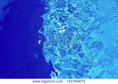 flickering background and abstract texture of brilliant water of bright blue color