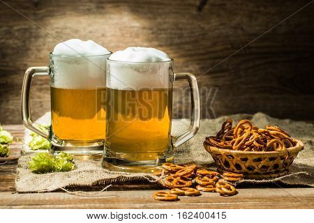 Couple glasses of beer froth with hop and pretzels on wooden table