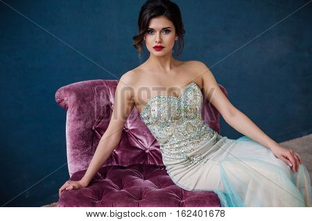 Beautiful woman in elegant evening dress. Professional make-up and hairstyle. Perfect skin. Fashion photo.