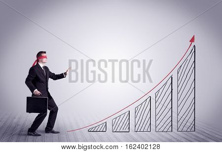 A young male office worker trying to find the right solution to develop a growing market concept with drawn exponential arrow.