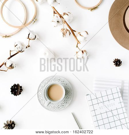 Flat lay trendy creative feminine accessories arrangement with coffee cotton branch and diary. Hat cotton branch notebook coffee cup fir cone golden clips on white background. Top view
