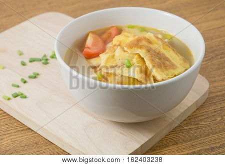 Thai Cuisine and Food Thai Omelet Soup with Tomatoes Onion and Chopped Scallion on Wooden Cutting Board.