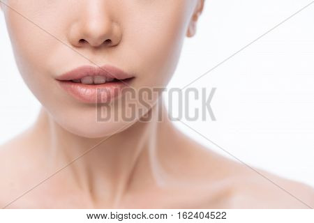 My beautiful skin. Delighted feminine charming Korean woman opening her mouth and expressing femininity while standing isolated in white background