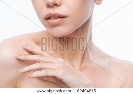 My tender skin. Attractive pleasant charming Korean woman touching her skin and expressing femininity while standing isolated in white background