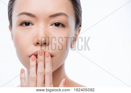 Soft like a silk. Involved positive young Korean woman touching her lips and expressing tenderness while standing isolated in white background