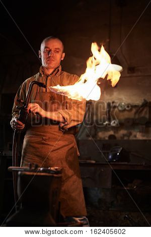 The blacksmith heats the gas burner before working in the workshop