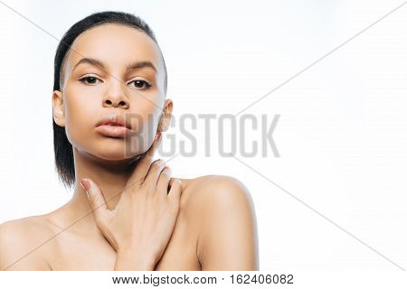 My soft skin. Charming graceful young Negroid woman touching her skin while standing against white background and expressing femininity