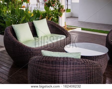Patio Furniture set with green pillow in the garden.