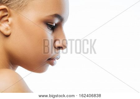 Concentrated on my thoughts. Thoughtful attractive young Negroid woman looking down while standing against white background and demonstrating concentration