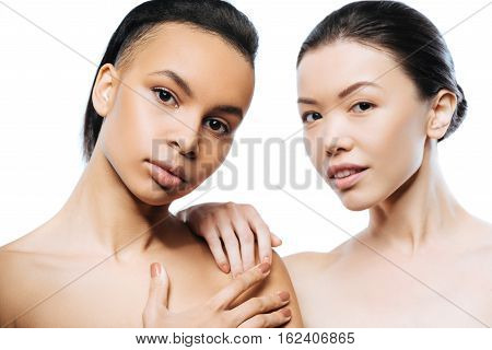 We having tender skin. Involved attractive positive girls standing close to each other and expressing tenderness while being isolated in white background